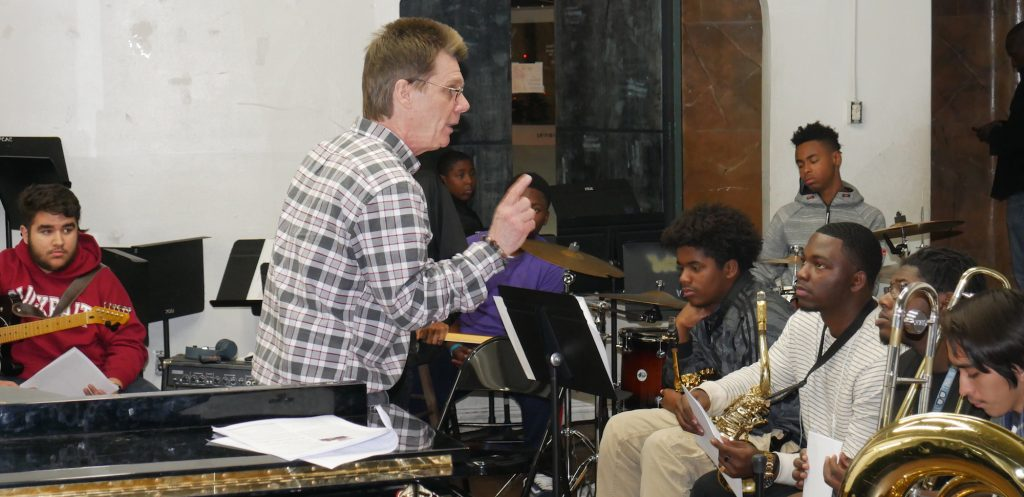 A man, standing, talks to a group of young seated students holding musical instruments