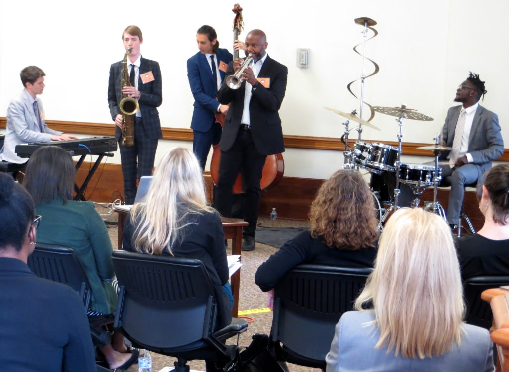 Five jazz musicians hold instruments and perform for a group of seated people