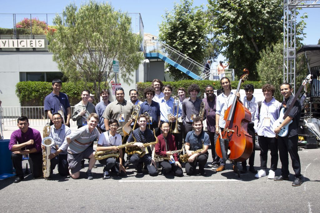 A group of students and their teachers pose for a photo with musical instruments