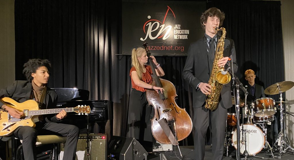 Four students playing jazz instruments perform on a stage with a black backdrop.